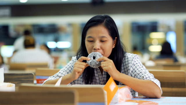 Asian-women-are-eating-donuts-happily-at-the-restaurant-