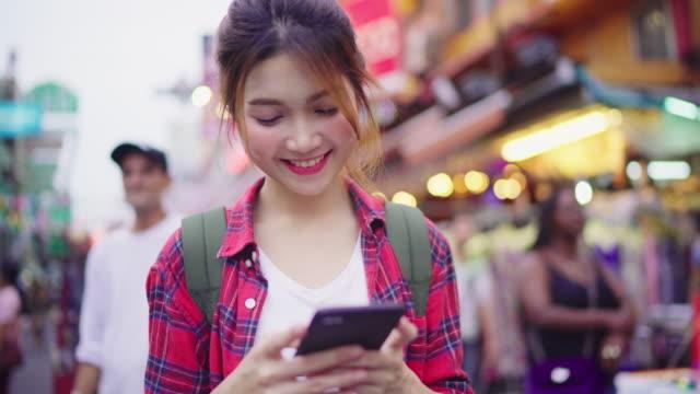 Backpacker-de-turismo-asiático-mujer-sonriendo-y-con-smartphone-viajando-solo-vacaciones-al-aire-libre-por-la-ciudad-calle-de-Khao-San-road-en-Bangkok-Bangkok---Tailandia-