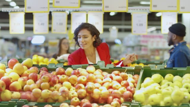 At-the-Supermarket:-Beautiful-Woman-Chooses-Organic-Fruits-in-the-Fresh-Produce-Section-of-the-Farmer-s-Market-She-Picks-Up-Fruits-and-Places-them-into-Her-Shopping-Basket-Slow-Motion-