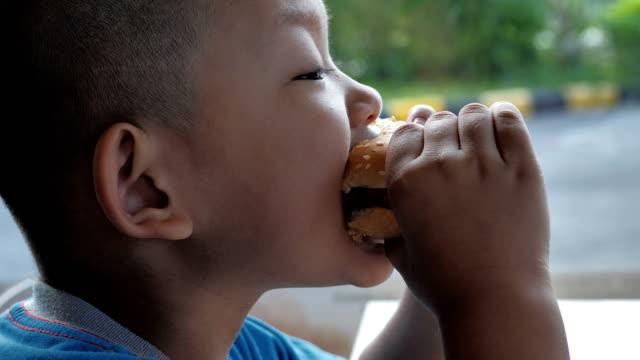 Nahaufnahme-junge-Asiaten-essen-Burger-niedlich-fröhlicher-junge-Hamburger-Restaurant-halten-Video-Zeitlupe