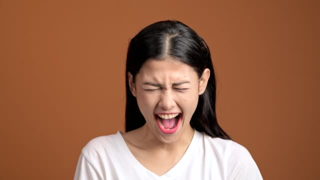 Angry-woman-isolated-Portrait-of-asian-woman-in-white-t-shirt-screaming-out-loud-looking-at-camera-