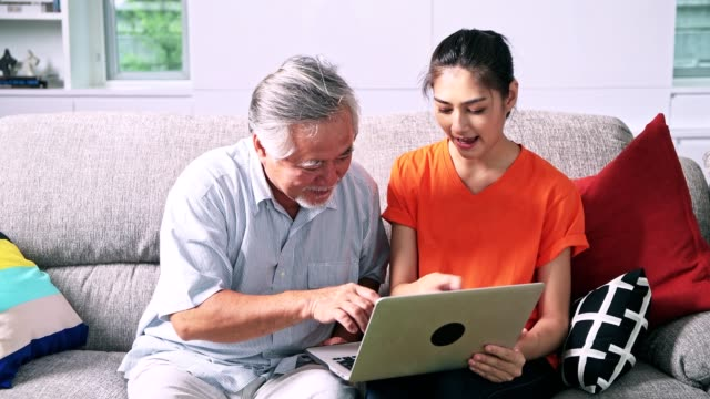 Daughter-teaching-her-father-computer-skills-in-living-room-Asian-man-with-white-beard-and-young-woman-sitting-in-living-room-using-laptop-Senior-lifestyle-family-concept-