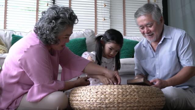Pareja-senior-y-niños-niña-jugando-rompecabezas-juntos-en-la-sala-de-estar-en-casa-Concepto-de-caucásico-familia-educación-crecer-aprender-y-el-desarrollo-de-la-edad-resolución-de-4-k-