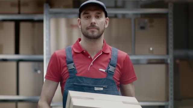 Retrato-de-almacén-guapo-trabajador-uniforme-da-sonrisas-y-paquete-de-la-caja-de-cartón-