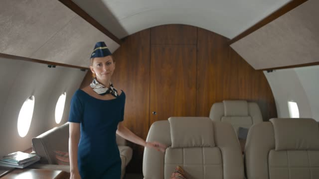 Pretty-stewardess-checking-airplane-s-salon-and-walking-to-camera-with-smile