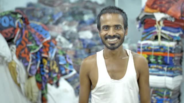 Un-hombre-feliz-o-un-trabajador-en-busca-de-la-cámara-con-una-sonrisa-en-un-taller-textil