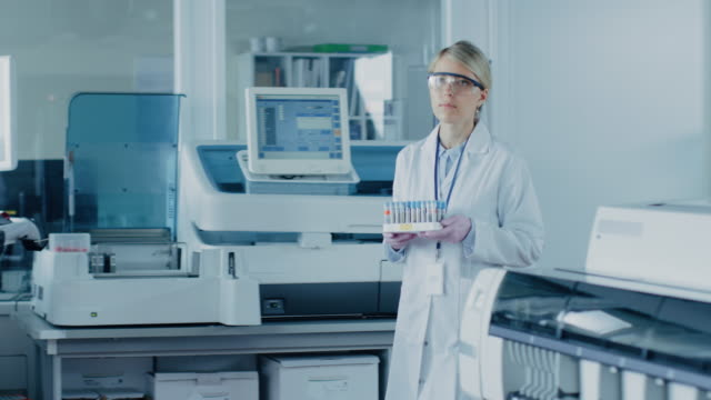 Female-Research-Scientist-Walks-Through-Laboratory-with-Tray-of-Test-Tubes-Filled-with-Samples-In-the-Background-People-Working-in-Laboratory-with-Innovative-Equipment-In-Slow-Motion-