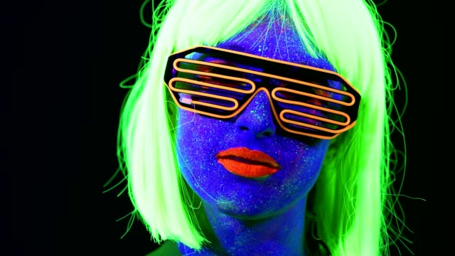 Woman-with-UV-face-paint-wig-UV-glasses-glowing-clothing-portrait-face-close-up-of-make-up-Caucasian-woman-