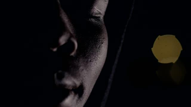 Deprimiert-nachdenklicher-afrikanischer-Mann-in-der-Dunkelheit-die-Augen-zu-öffnen
