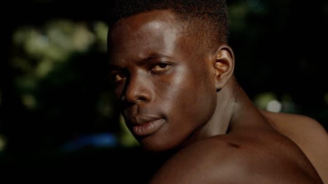 Angry-black-shirtless-african-man-turning-and-staring-at-camera