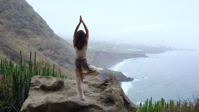 Woman-meditating-in-yoga-warrior-pose-at-the-ocean-beach-and-rock-mountains-Motivation-and-inspirational-fit-and-exercising-Healthy-lifestyle-outdoors-in-nature-fitness-concept-