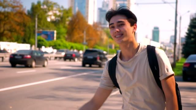 Dulce-muchacho-asiático-es-coger-el-coche-en-el-camino-sonriendo-y-mostrando-llaves-mientras-que-está-parado-en-la-carretera-solo-un-clima-perfecto-para-viajar