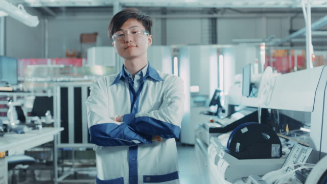 On-High-Tech-Factory:-Portrait-of-Asian-Worker-with-Crossed-Arms-In-the-Background-Electronic-Printed-Circuit-Board-Assembly-Line-that-Uses-Surface-Mount-Technology-and-Pick-and-Place-Machinery-