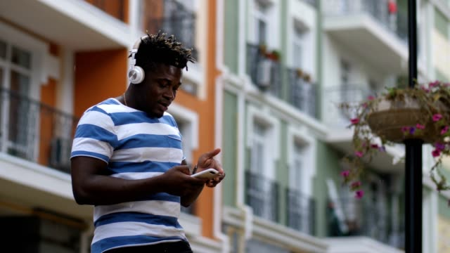 Man-in-earphones-listening-music-online-using-phone