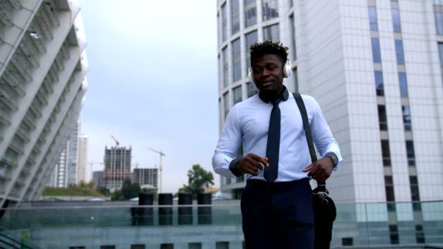 Carefree-black-businessman-dancing-in-city-street