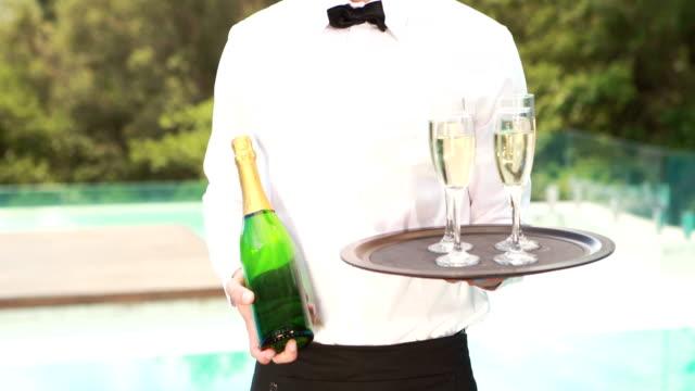 Smiling-waiter-holding-champagne-bottle-and-flute
