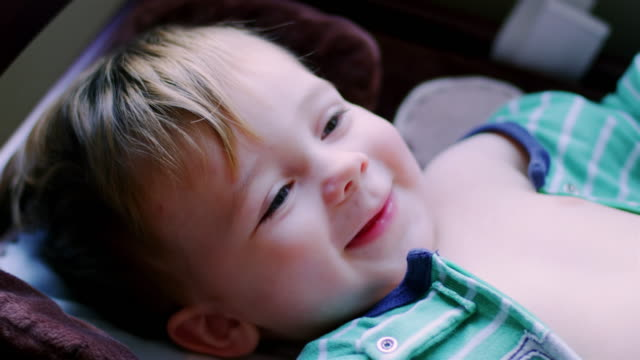 Adorable-baby-boy-in-pajamas-laying-on-a-changing-table-looking-up