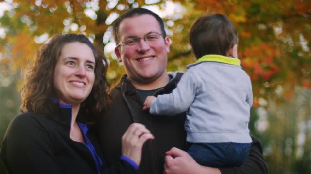 Familia-posando-para-una-foto-frente-a-árbol-niño-no-mirando-a-la-cámara