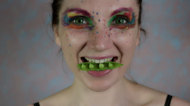 4k-Shot-of-a-Woman-with-Multicoloured-Make-up-with-Beans-in-mouth