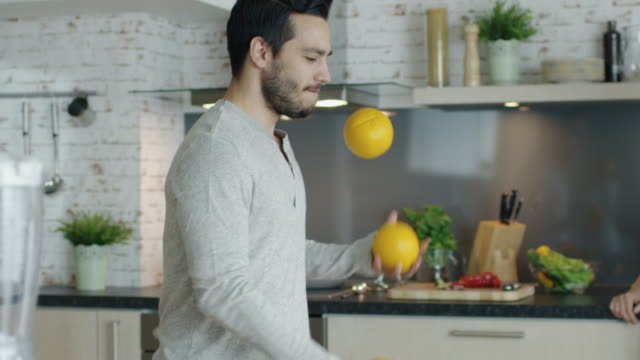 Lively-Young-Man-Impresses-His-Girlfriend-by-Juggling-Oranges-on-the-Kitchen-