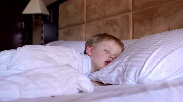 The-little-boy-is-sleeping-in-the-bed-