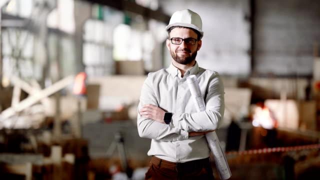 Un-arquitecto-adulto-en-un-casco-encuentra-en-la-construcción-actual-en-sus-manos-un-proyecto-para-la-modernización-de-una-fábrica-abandonada-en-la-ciudad