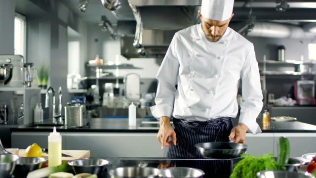 Professional-Chef-Working-in-a-Famous-Restaurant-Kitchen-Starts-Preparing-His-Specialized-Dish-Turns-on-Stove-and-Puts-Pan-with-Oil-on-it-