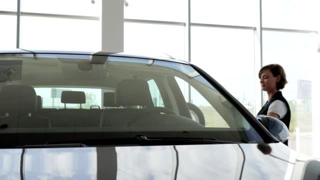 Young-woman-holding-keys-to-new-vehicle-smiling-at-camera-joyful
