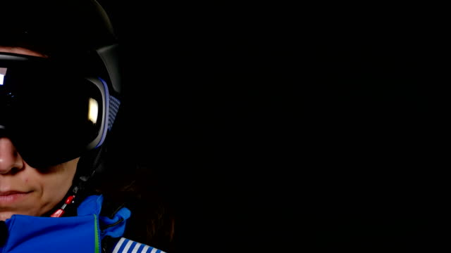 Half-face-portrait-of-skier/snowboarder-woman-with-glasses-on-black-background