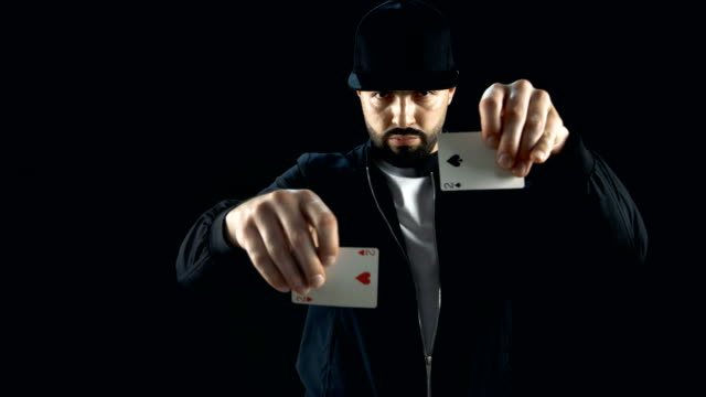 Professional-Street-Magician-in-a-Cap-Performs-Impressive-Sleight-of-Hand-Card-Trick-Background-is-Black-