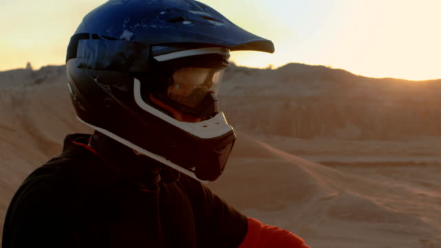 Close-up-Portrait-Shot-Of-the-Extreme-Motocross-Rider-in-a-Cool-Protective-Helmet-Standing-on-the-Off-Road-Terrain-He-s-About-to-Overcome-Background-is-Sandy-Track-