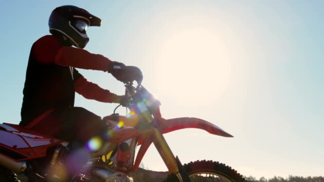 Low-Angle-Footage-of-the-Professional-Motocross-Rider-on-FMX-Motorcycle-Stands-in-the-Middle-of-the-Quarry-and-Overlooks-Extreme-Off-Road-Terrain-that-He-Gonna-Ride-Today-