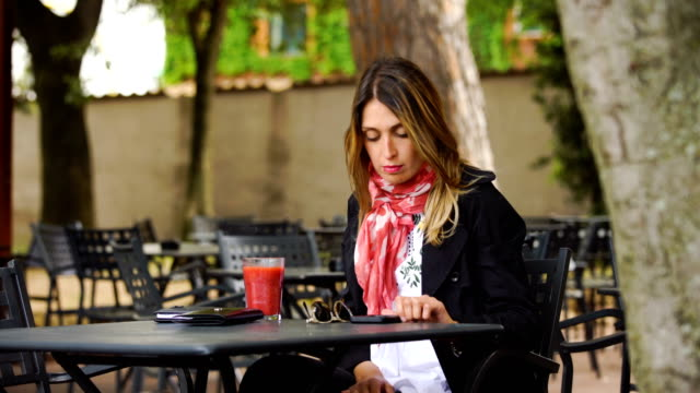 portrait-of-smiling-Businesswoman-With-Cellphone-Working-In-Cafe-Outdoors