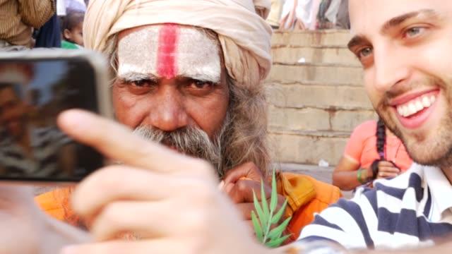 Tourist-taking-a-selfie-with-Sadhu---Holy-Man-in-Varanasi-India