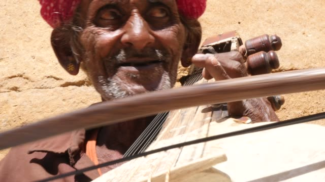 Indian-senior-plays-traditional-musical-instrument-in-Jaisalmer-Fort-Rajasthan-India