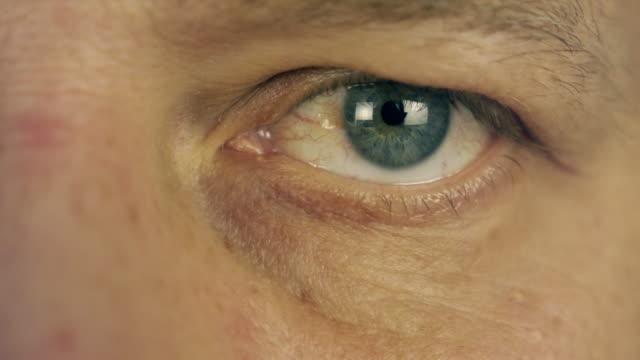 Intermitente-ojo-del-hombre-Ojo-izquierdo-de-hombre-extremo-de-cerca-cara-masculina-de-vista-macro-Hombre-leer-Buscando-información-Cara-sonriente-Movimiento-del-ojo-