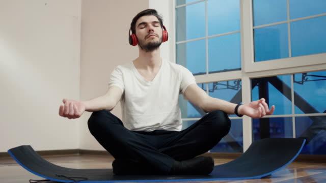 Chico-joven-meditando-sobre-el-piso-y-escuchar-música-en-auriculares