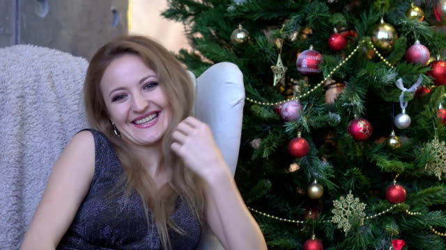 Young-attractive-happy-woman-laughing-smiling-and-sitting-on-christmas-tree-background-