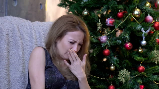 Young-woman-sneezing-on-christmas-tree-background-