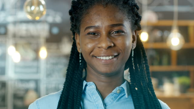 Portrait-of-a-Beautiful-African-American-Cafe-Owner-Walking-into-Focus-while-in-the-Background-Her-Stylish-Coffee-House-Shines-with-Lights-