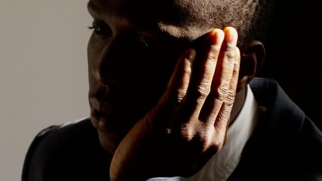 depressed-and-sad-black-business-man-in-the-dark--close-up