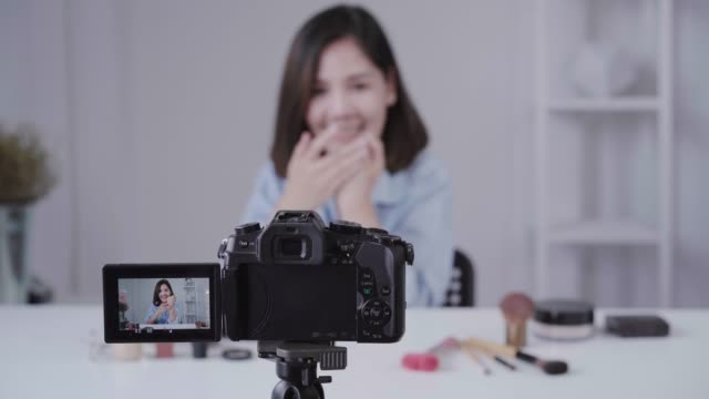 Happy-smiling-asian-woman-or-beauty-blogger-with-brush-and-camera-recording-video-and-waving-hand-at-home-Beauty-videoblog-blogging-people-concept-