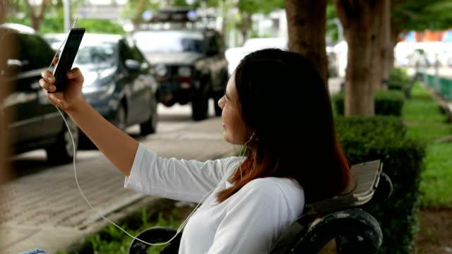 Hermosa-mujer-tener-chat-de-vídeo-usando-el-teléfono-inteligente-al-aire-libre-en-parque-público-