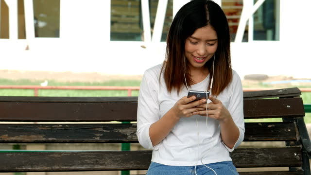 Young-asian-woman-using-smartphone-sitting-on-a-bench-in-a-public-park-
