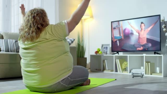 Talla-grande-mujer-haciendo-Yoga-con-un-Instructor-en-línea