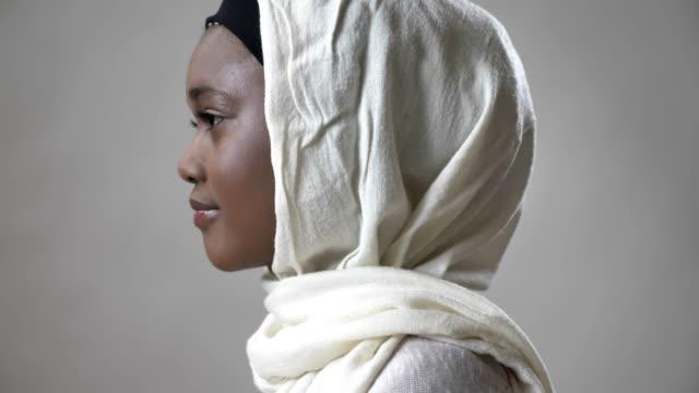 Niña-musulmana-africana-en-hijab-es-girar-la-cabeza-y-mirando-a-cámara-religioun-concepto-fondo-gris