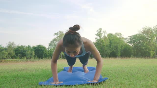 Junge-asiatische-Frau-Yoga-im-Freien-bleiben-Sie-ruhig-und-meditiert-beim-Üben-von-Yoga,-die-innere-Ruhe-zu-erkunden.-Yoga-und-Meditation-haben-gute-Vorteile-für-die-Gesundheit.-Yoga-Sport-und-gesunde-Lifestyle-Konzept.