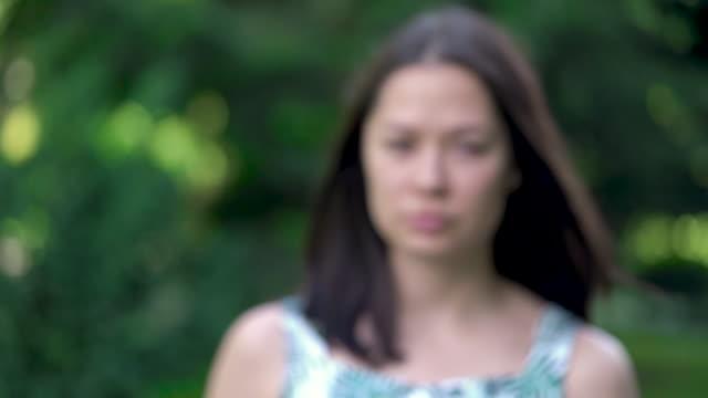 Borroso-retrato-de-mujer-asiática-pone-sus-gafas-Enfoque-aparece-después-de-poner-las-gafas-Árboles-verdes-en-el-fondo-