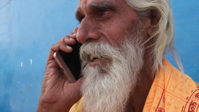 Tilt-up-to-Sadhu-Hindu-priest-talking-on-smart-phone-with-a-blue-background