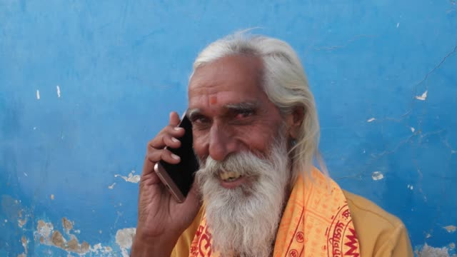 Handheld-closeup-of-a-Hindu-Sadhu-smiling-while-attending-a-call-on-his-mobile-phone